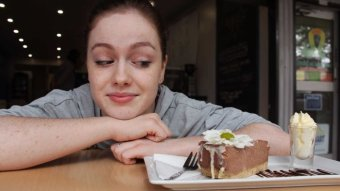 Phoebe Clarke leans on a table and looks at a piece of cake.